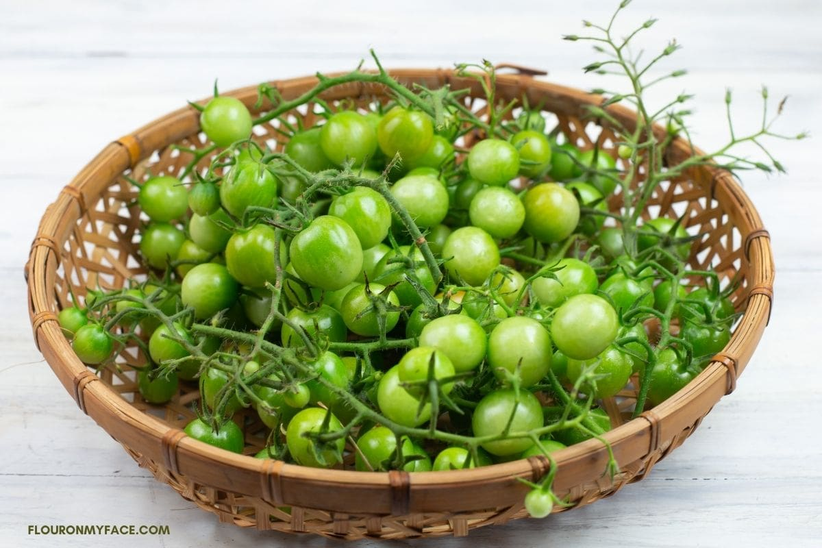 Roud basket filled with green cherry tomatoes.