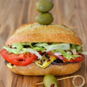 Grilled Vegetable Sandwich with olives on a cutting board.