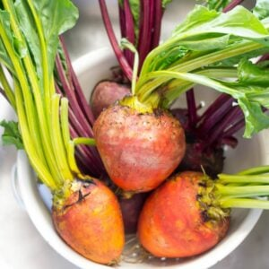Red and golden beets in a colander.