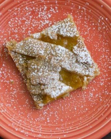 A square piece of peach slab pie on a plate.