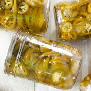 Canning jars filled with pickled jalapeno peppers.