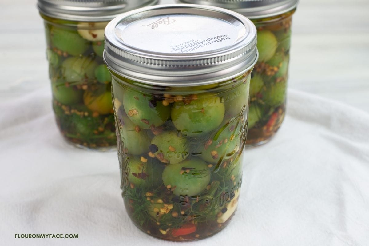 Pickled green cherry tomatoes in a canning jar.