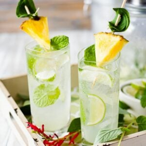 2 tall glasses filled with pineapple sage mojito, garnished with pineapple wedge and lime wedges.