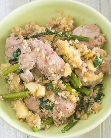 A bowl filled with a serving of pork loin with spinach and asparagus over quinoa.