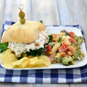 Rotisserie Chicken Salad recipe served on a roll with sides.