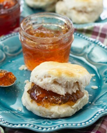 A jar of scuppernog jelly with a biscuit on a plate.