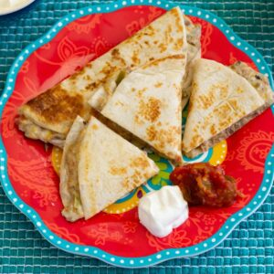 Shredded Beef Quesadillas with salsa and sour cream on a plate.