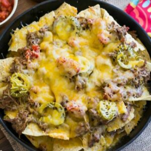 Shredded Beef Nachos cooked in a cast iron skillet with all the toppings.
