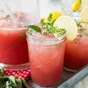 Mason jars filled with Watermelon Thyme Lemonade.