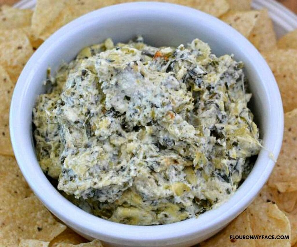 Artichoke Spinach Dip in a dip bowl surrounded by chips.