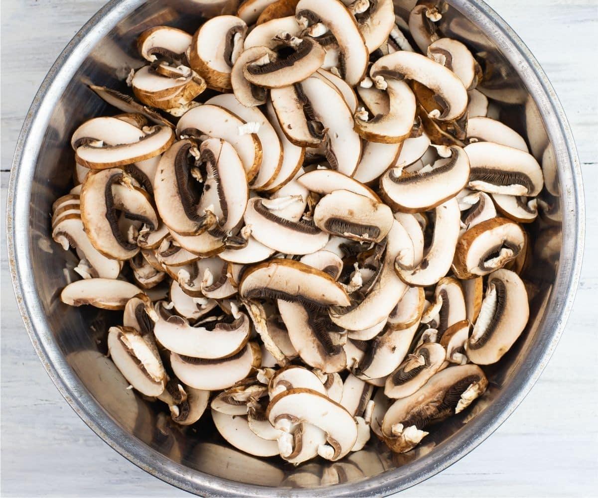 sliced baby bella mushrooms in a metal bowl.