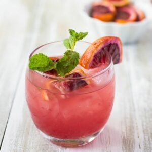 Blood orange smash cocktail served in a highball glass garnished with mint leaves and wedges of blood orange.