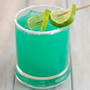 Blue Devil Cocktail served in a highball glass with a lime wedge.