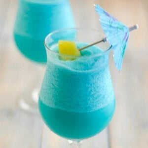 Blue Hawaiian Cocktail in a hurricane glass garnished with pineapple and umbrella.