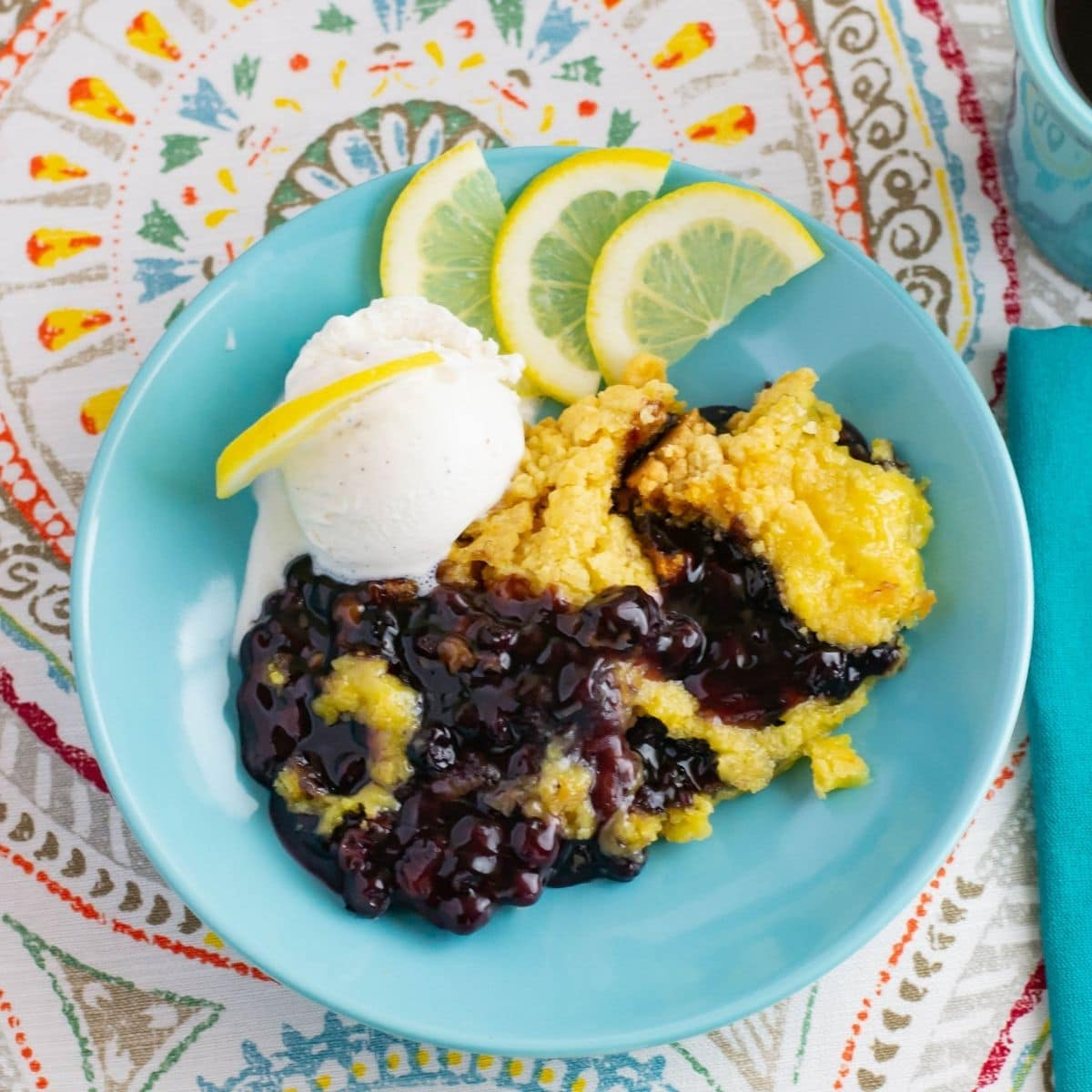 Blueberry Lemon Dump Cake with a scoop of vanilla ice cream in a bowl.