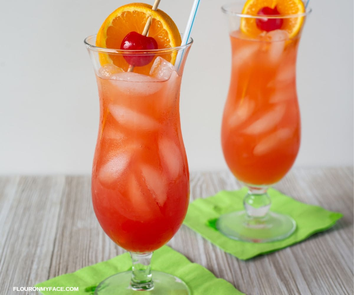 Two hurricane glasses filled with the classic hurricane cocktail, garnished with a cherry and slice of orange.