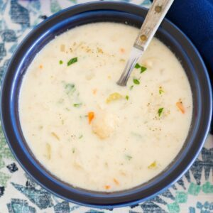 A blue bowl filled with crock pot cheesy cauliflower soup.