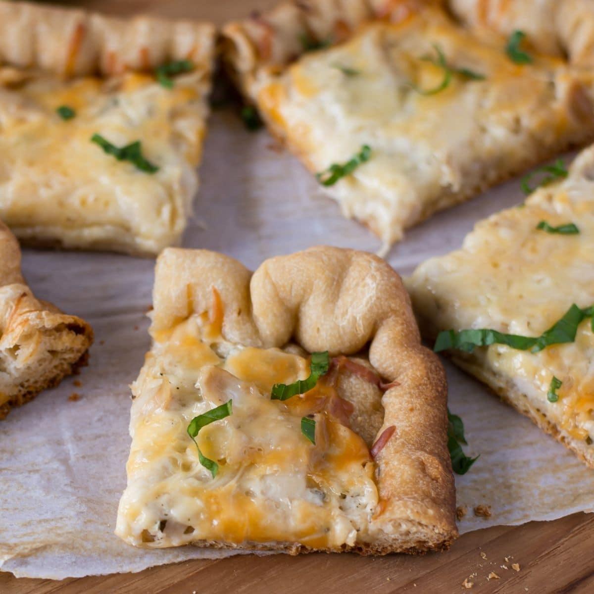 Crispy Crock Por Chicken Alfredo Pizza cut into squares.