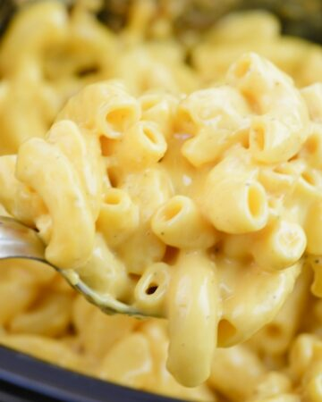 Close up of a serving spoonful of creamy crock pot macaroni and cheese.