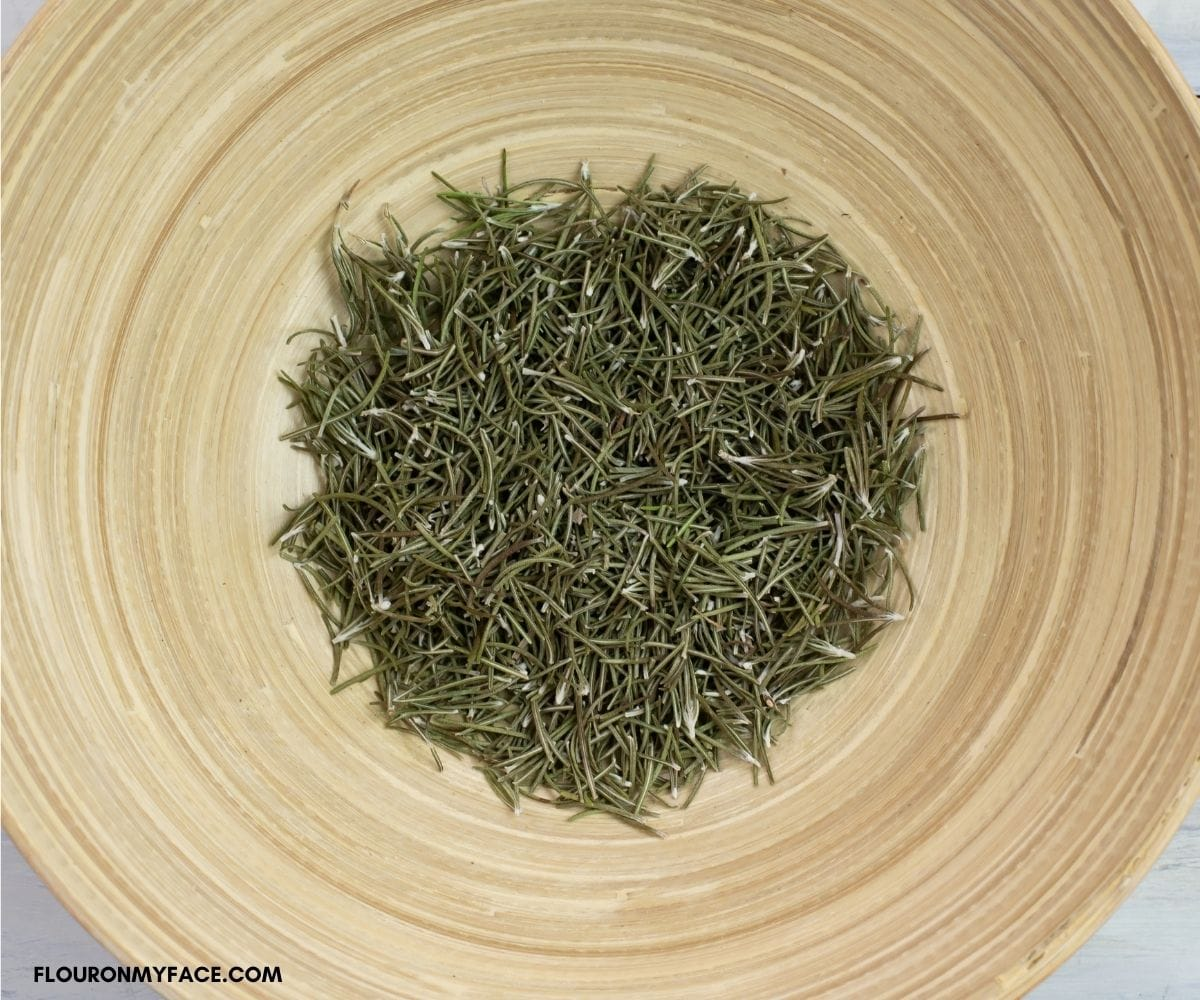 Dried rosemary in a wooden bowl.