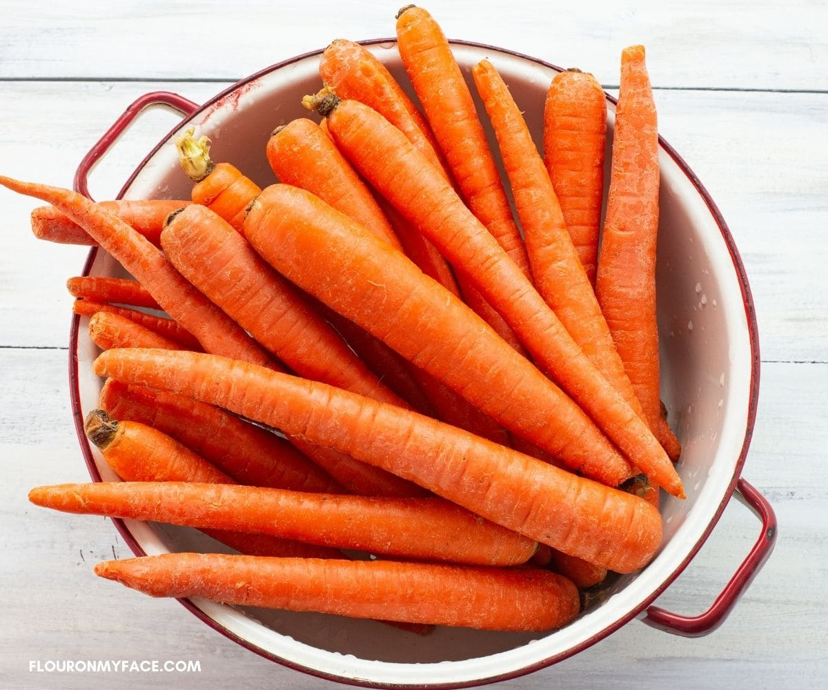 Fresh whole carrots in a white enamel colander.