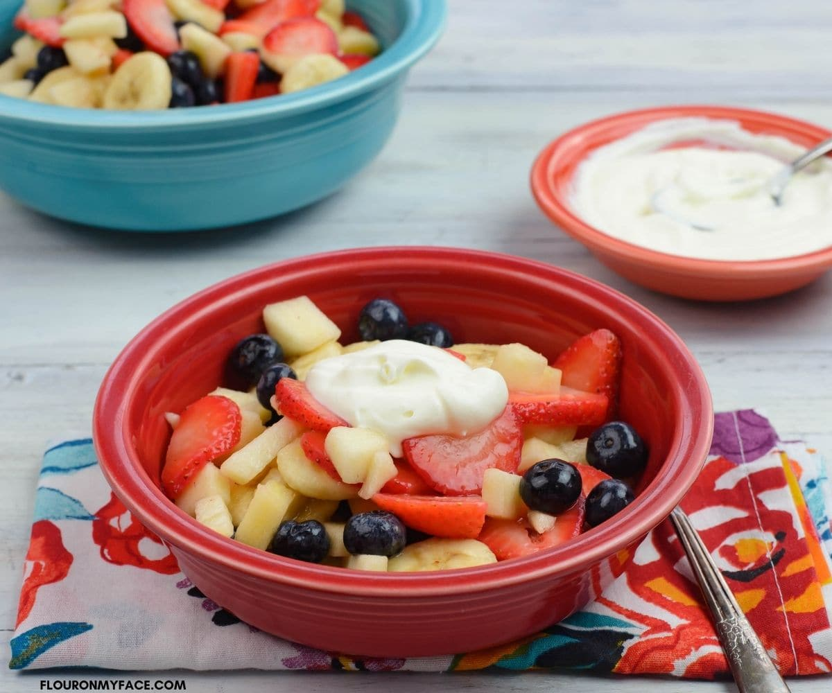 A bowl of fresh fruit topped with sweetened crème fraiche.
