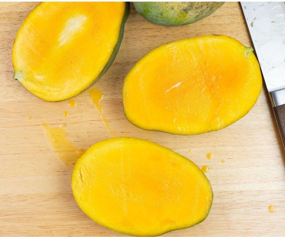 Fresh mangoes sliced in half on a cutting board.