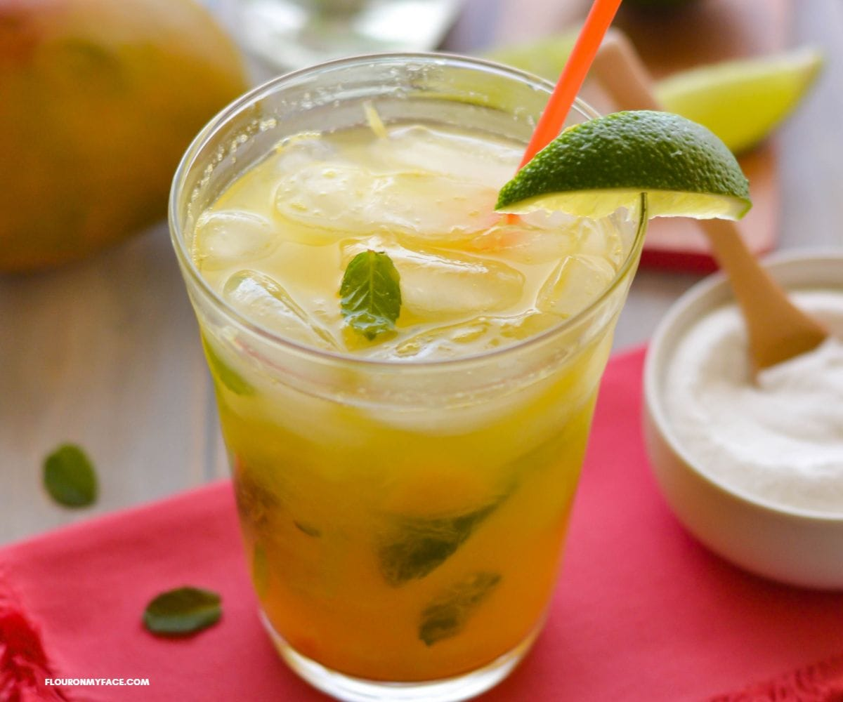 A cocktail glass filled with Mango Mojito with lime and mint garnish.