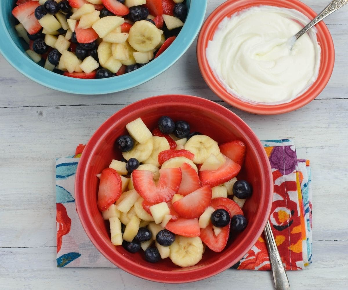 A bowl of fruit salad with a small bowl of crème fraiche.