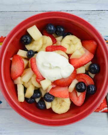 Fruit salad with crème fraiche in a red bowl.