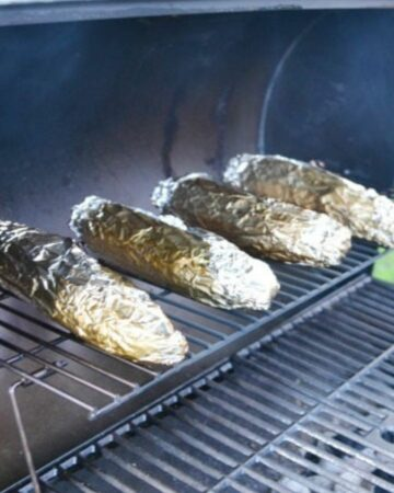 Corn on the cob wrapped in aluminum on a hot grill.