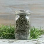Dehydrated rosemary in a glass spice bottle.