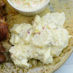 A closeup of a serving of old fashioned potato salad on a dinner plate.