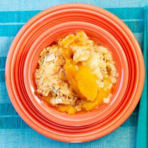Peach cobbler in a dessert bowl on a placemat.