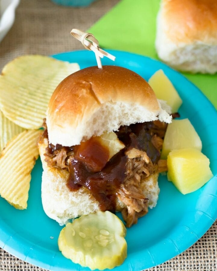 A pineapple pulled pork slider with chips and pineapple chunks on a plate.