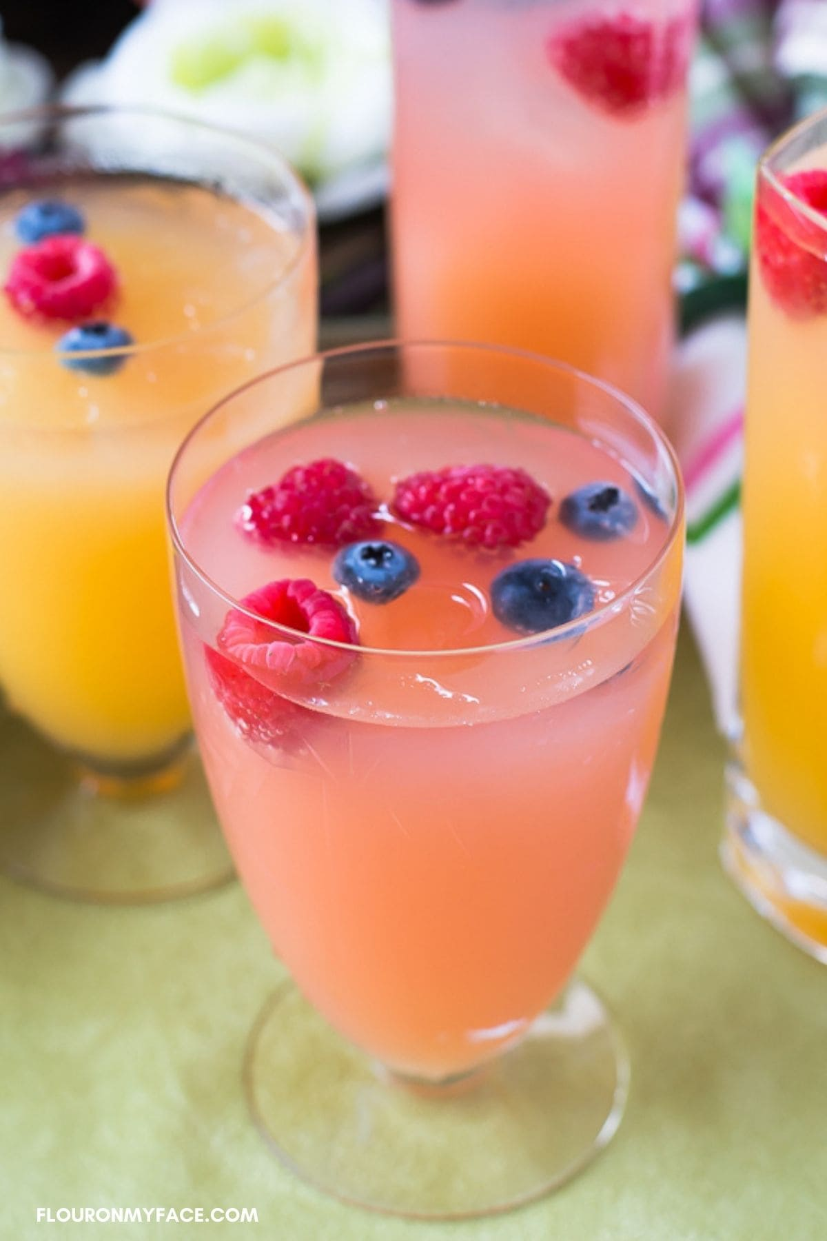 Tall cocktail glasses filled with Spring Mimosas on a table top.