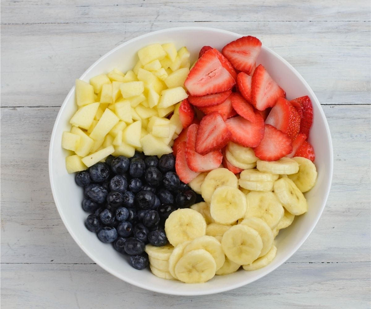 A large white bowl filled with sliced strawberries, bananas, blueberries and cubed apple.