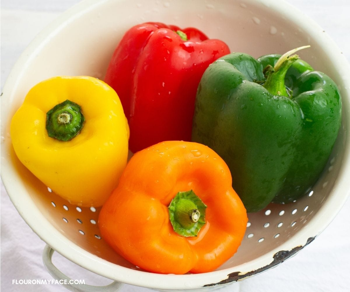 Four sweet bell peppers in a white enamel colander.