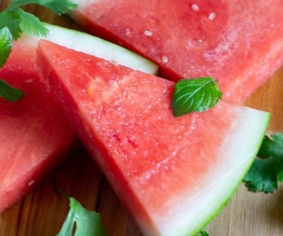 A triangle shaped watermelon slice on a cutting board.