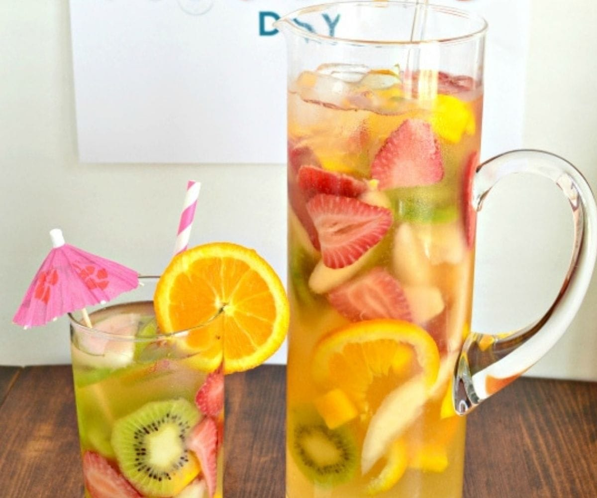 A glass and a tall skinny glass pitcher filled with white moscato sangria.