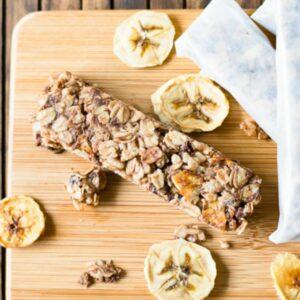 Banana Chocolate Granola Bars, sliced banana chips on a wooden cutting board.