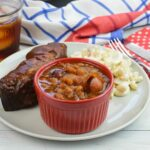 A small bowl filled with baked beans on a plate with ribs.