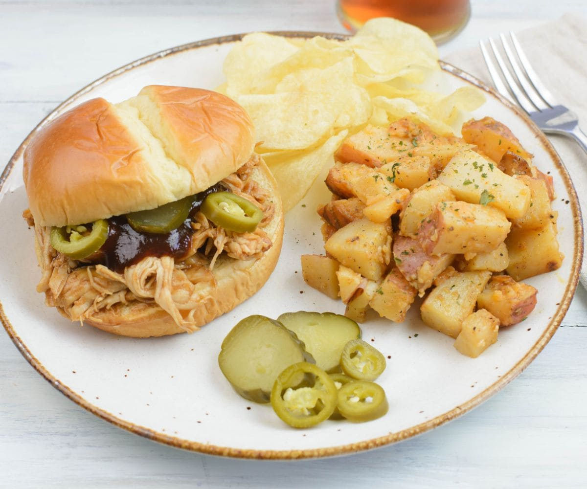 Garlic potatoes served with a sandwich, chips and pickles on a plate.