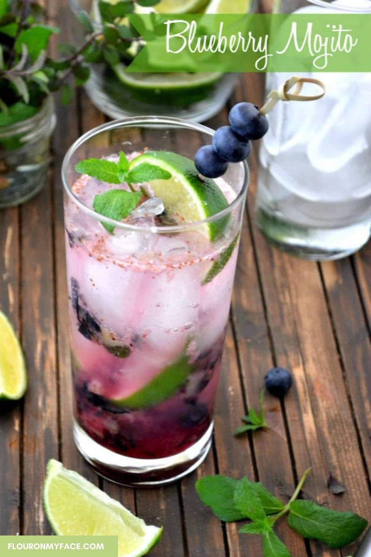 A tall glass filled with blueberry Mojito, lime wedges and a glass in the background.