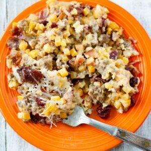 Butternut Squash Casserole with brown sugar bacon on a round orange plate.