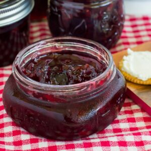 A canning jar filled with cherry habanero jam served with crackers and cream cheese.