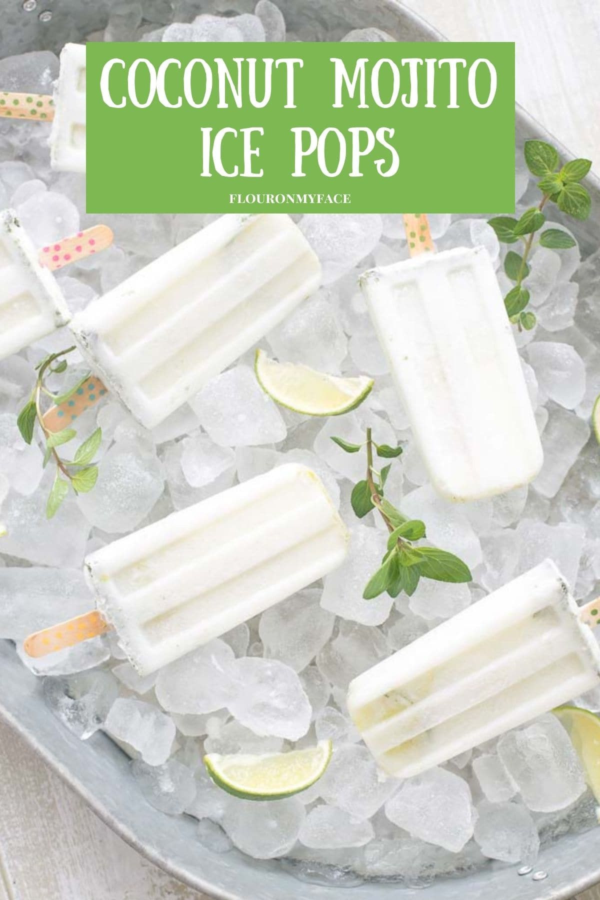 A galvanized serving tray piled high with ice cubes with coconut mojito ice pops nestled in the ice.