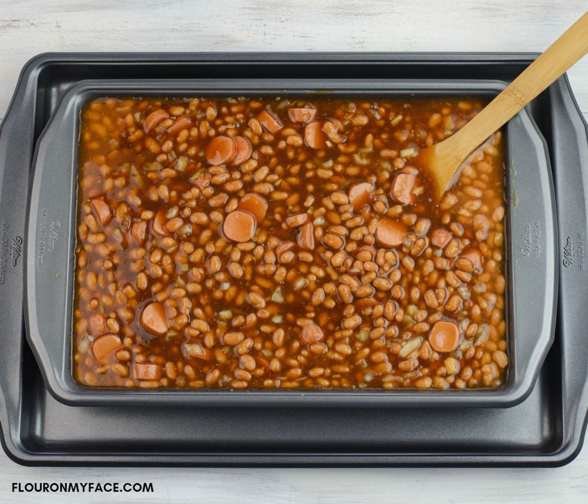 Baked beans ingredients in a large baking pan.