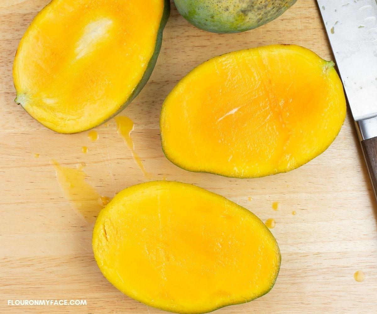 Cut the flesh from each side of a fresh mango.