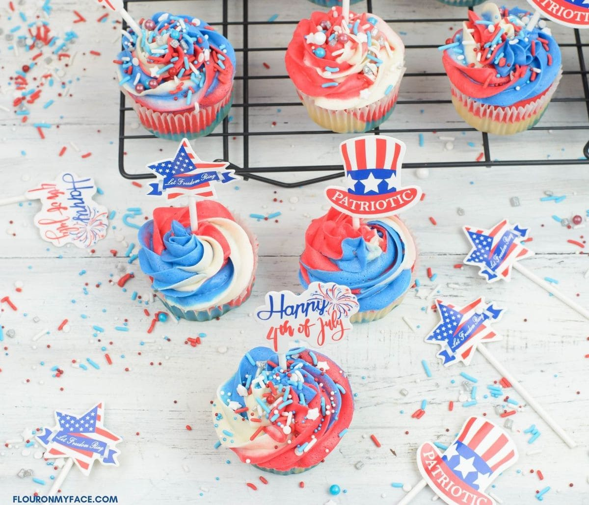 Red, white and blue cupcakes decorated with sprinkles.